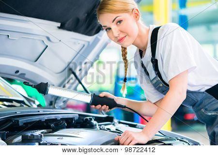 Female mechanic examine car engine with light in workshop