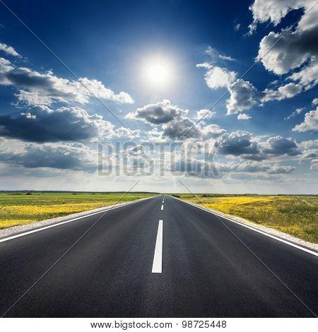 Driving On Straight Asphalt Road Towards The Sun