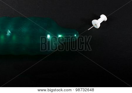Metal Pin Piercing A Green Condom