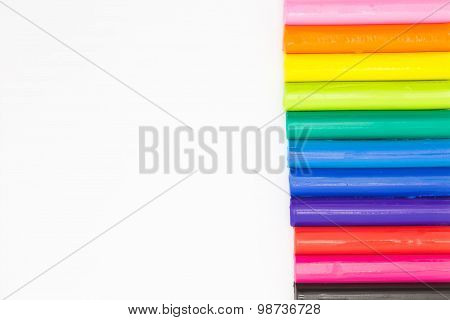Art rainbow colour clay sticks on right of white background