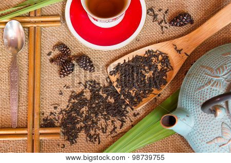 Shot From The Dry Black Tea With Flowers , A Cup On Burlap Background