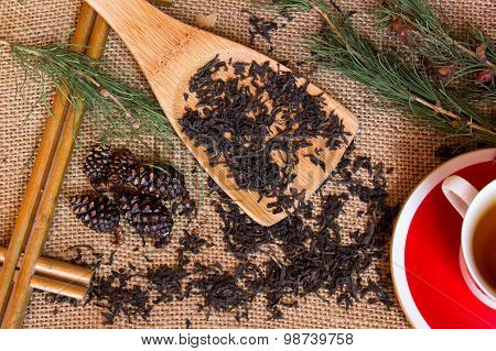Shot From The Dry Black Tea With Pine Branches , A Cup On Burlap Background