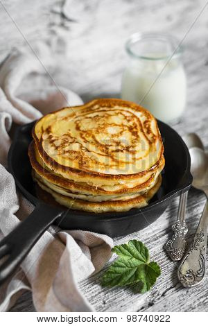 Pancakes With Honey In A Pan On A Light Wooden Background
