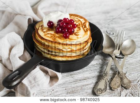 Pancakes With Honey And Red Currants In A Pan On A Light Wooden Background