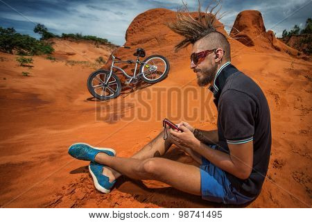 Biker take a rest and listen music on road in the high mountains of sand dunes . Background blue sky with clouds