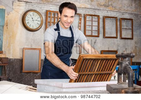 Portrait of smiling male worker dipping mold in pulp and water at paper factory