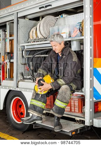Full length of fireman holding coffee cup while sitting in truck at fire station