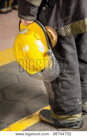 Low section rear view of fireman holding helmet at fire station