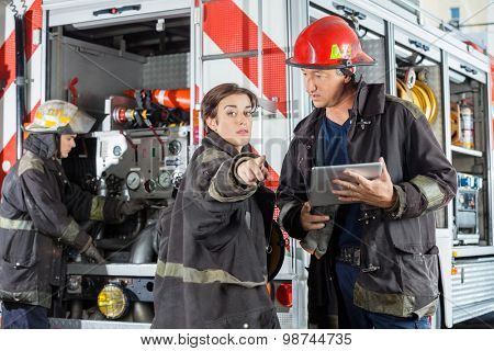 Female firefighter pointing while colleague holding digital tablet against truck at fire station