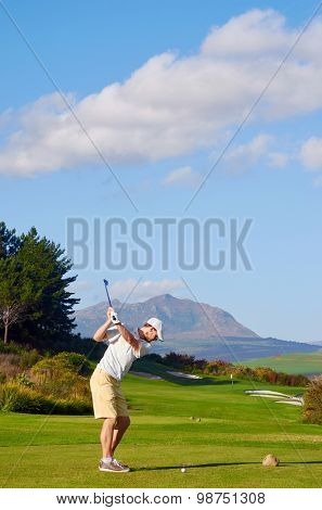 golfer hitting driver off tee box on a beautiful scenic course