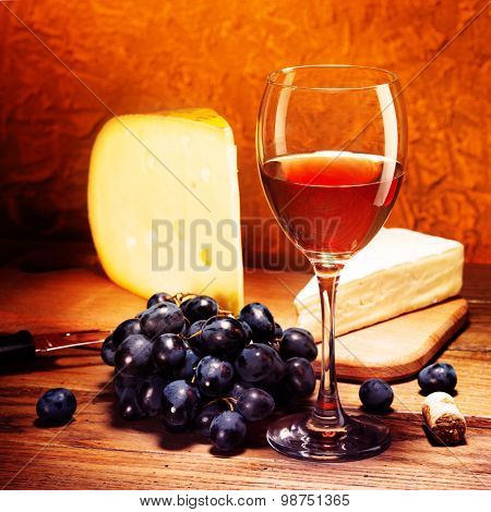 Still-life with cheese, grapes and glass of red wine.Filtered image: vintage effect.