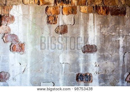 Old Brick Wall With The Damaged Plaster