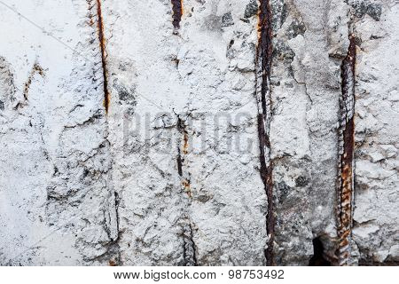 Whitewashed Surface With Visible Rusty Reinforcement Bars