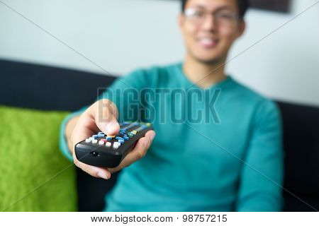 Asian Man Watching Tv Changes Channel With Remote