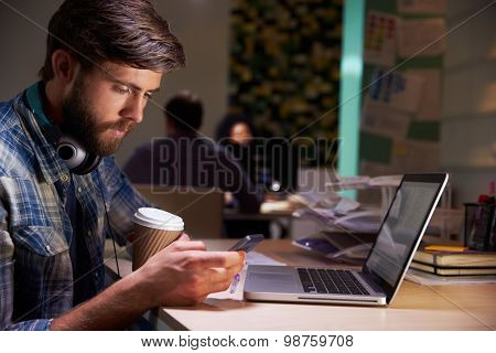 Office Worker With Coffee At Desk Working Late On Laptop