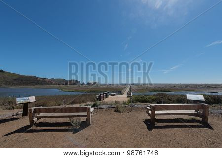 Two Wooden Benches Face A Lagoon And Beach