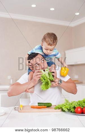 Handsome father and his child are making fun in kitchen
