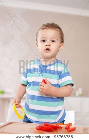 Cheerful small kid is tasting healthy food