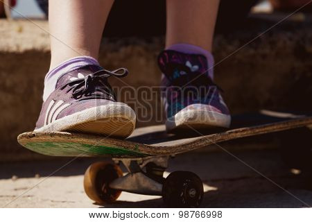 Beautiful young girl sitting on Skateboard