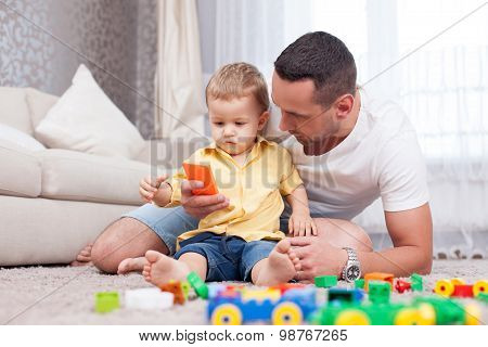 Handsome father is acquainting his child with modern technologies