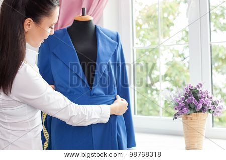 Attractive female tailor is creating fashionable clothing