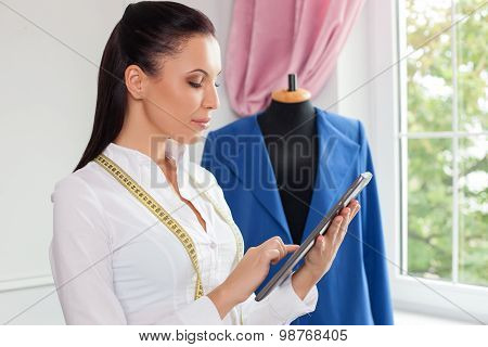 Attractive young female tailor is working with modern technology