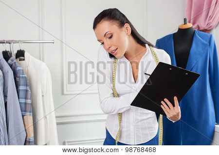 Attractive young female tailor is working with new project