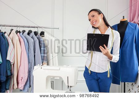 Beautiful female tailor is using a telephone for work