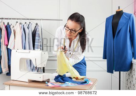 Attractive young clothes designer is creating new clothing