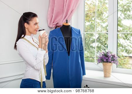Attractive young female tailor is resting after work