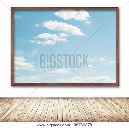 Wooden frame with cloud and sky picture hanging on wall near sidewalk