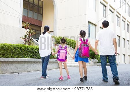 Father And Mother Walking To School With Children