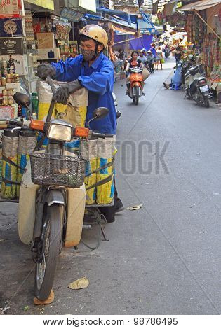 man is trying to set a load on motorcycle, Hanoi