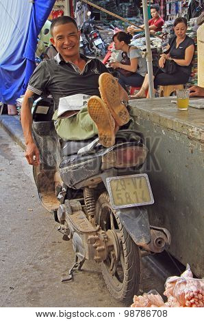 man is sitting on motorcycle with outstretched legs, Hanoi