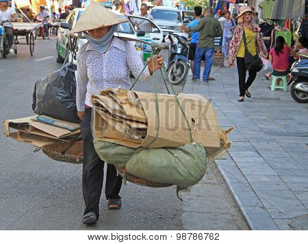 woman is carrying sheets of pasteboard in Hanoi
