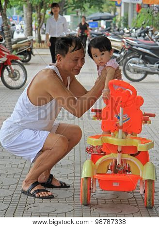 man is holding a boy in his hands on the street, Hanoi