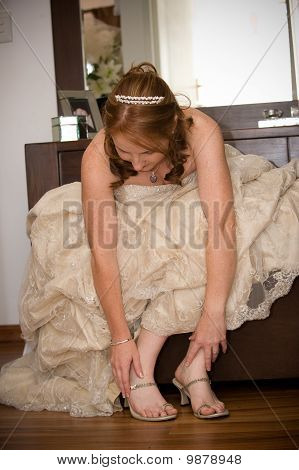 bride fastining  shoes wearing and tiara with both feet visible