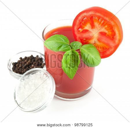 Tomato juice with basil leaves, tomato slice and bowls with black pepper and sea salt