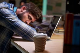 image of late 20s  - Male Office Worker Asleep At Desk Working Late On Laptop - JPG