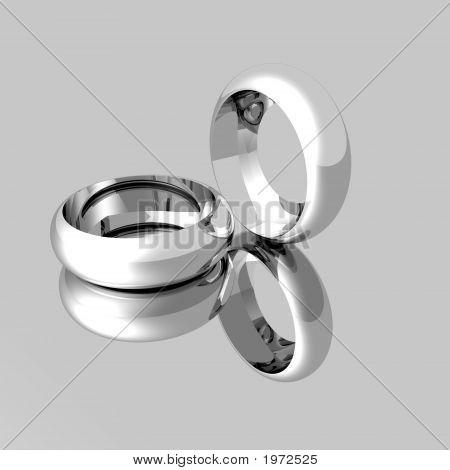 Platinum Wedding Rings On Mirrored Surface
