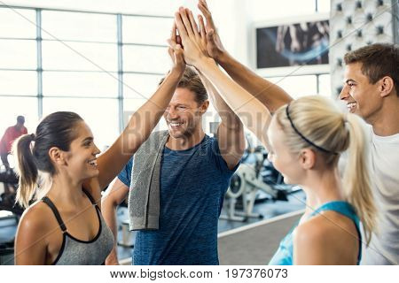 poster of Smiling men and women doing high five in gym. Group of young people making high five gesture in gym