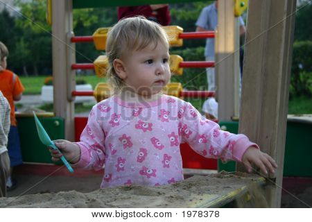 Toddler With Shovel In Sandbox