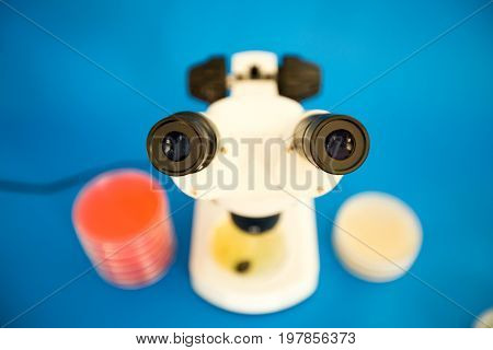 poster of Scientific microscope and petri dishes for scientific research on blue background