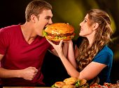 Couple eating fast food. Man and woman treat big hamburger with ham. Friends give burder junk on dar poster