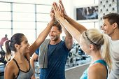 Smiling men and women doing high five in gym. Group of young people making high five gesture in gym  poster