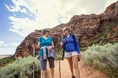 Two happy women hiking together in a red rock sandstone canyon in the deserts of Utah on an adventur poster