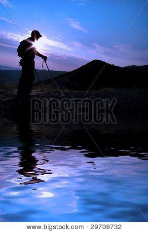 One Person walking along ridge in silhouette reflected in water