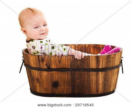 Cute Infant Girl Sitting In Wooden Bucket