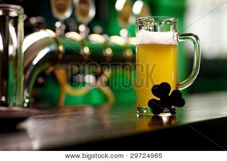 Imagem do copo de cerveja com uma folha de trevo na mesa de pub