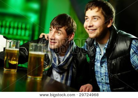 Two friends spending time at sport bar enthusiastic about the game